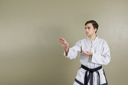 Young man performing double knife hand pose. Position for blocking attacks in taekwondo. Dressed in dobok uniform and black belt. Korean culture. Isolated on neutral background a