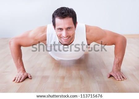 Young Man Performs Pushup On Hardwood Floor