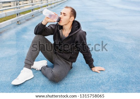 Young man personal trainer in a gray suit drinking water from his bottle after a fat burning morning street workout. Concept of water balance replenishment during workouts #1315758065