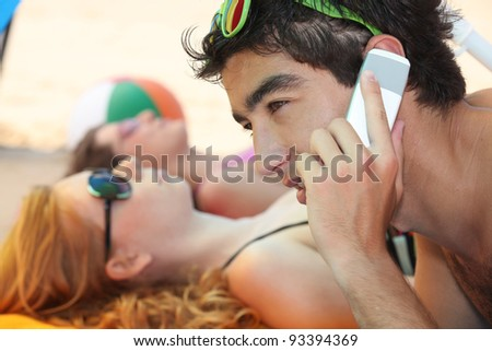 young man phoning at the beach with his friends - stock photo