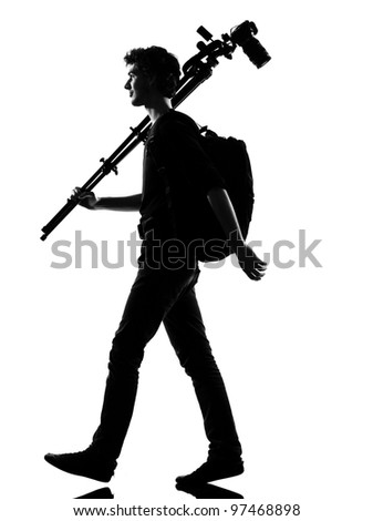 young man photographer silhouette in studio isolated on white background