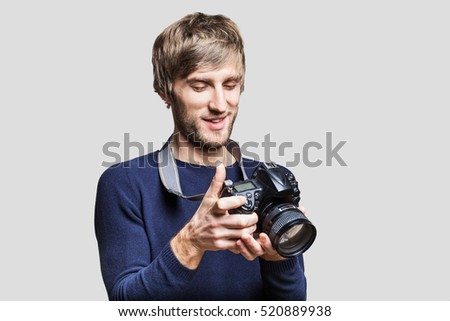 Young man photographer takes pictures with dslr camera #520889938