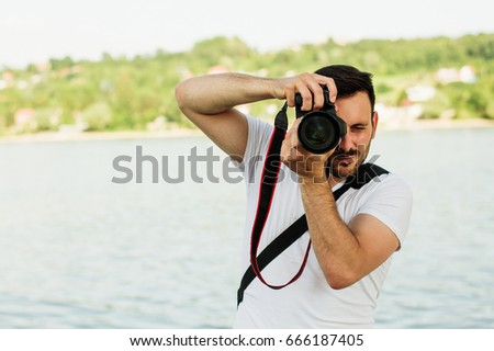 Young man photographer taking pictures with his DSLR #666187405