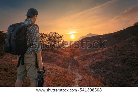 Young man, photographer, with backpack and tripod, standing on a hill and observing the location for shooting.