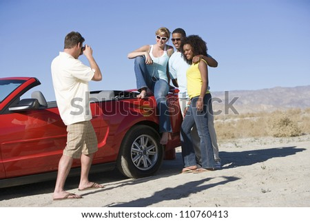 Young man photographing friends near car