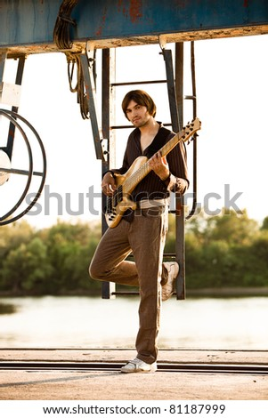 young man play bass guitar at industrial area by the river at sunset, full body shot