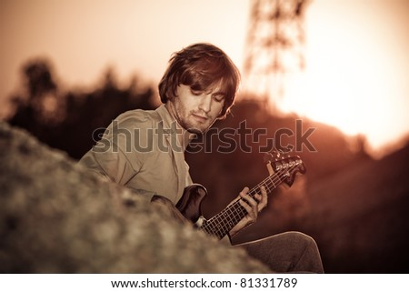 young man play guitar at sunset