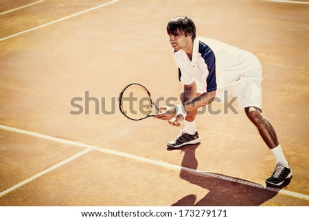 young man play tennis outdoor on orange tennis court
