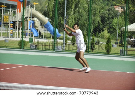 young man play tennis outdoor on orange tennis court at early morning