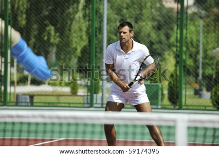 young man play tennis outdoor on orange tennis field at early morning