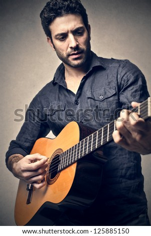 Young man playing a classic guitar