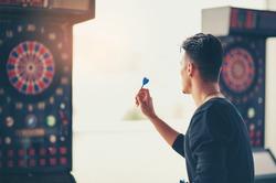 Young man playing a game shooting darts