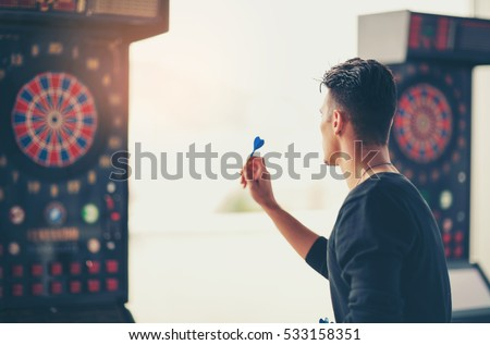 Young man playing a game shooting darts