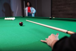 Young man playing billiard and blurred African-American woman on background
