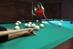 Young man playing billiard and blurred African-American woman on background, closeup