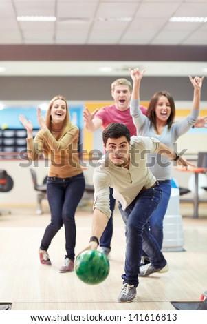 Young man playing bowling - stock photo