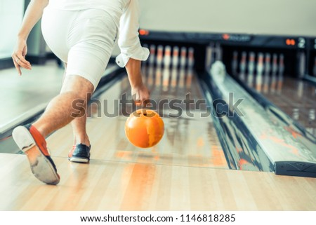 Young man playing bowling at the sport club.