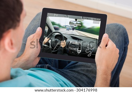 Young Man Playing Car Racing Game On Digital Tablet At Home