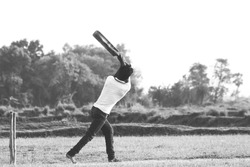 Young man playing cricket on a ground
