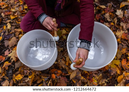 Young Man playing crystal bowls outdoors in the forest while autumn colors are at their best - Pictured from above - Young man is wearing fancy wooly red jacket and urban red pants
