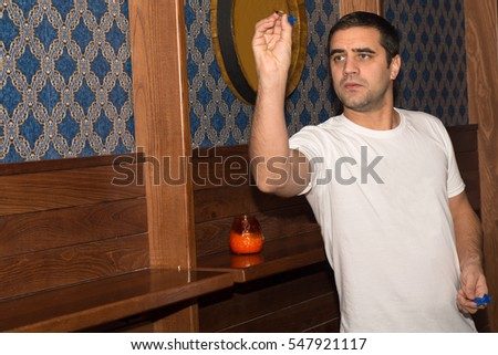 Young man playing darts in a club