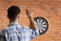 Young man playing darts indoors