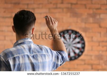 Young man playing darts indoors Stockfoto ©