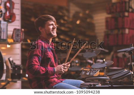 Young man playing drums in the store