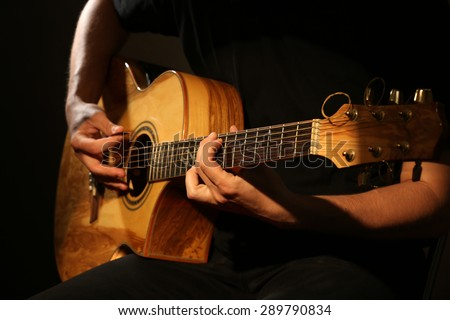 Young man playing on acoustic guitar on dark background #289790834