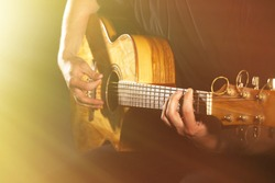 Young man playing on acoustic guitar on dark background with light effect