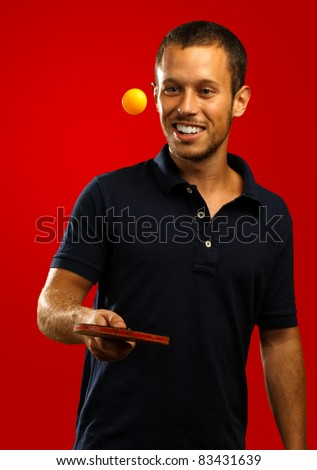 young man playing ping pong on a red background