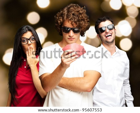 young man playing poker with friends against a abstract lights background
