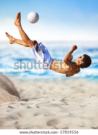 Young man playing soccer on beach.
