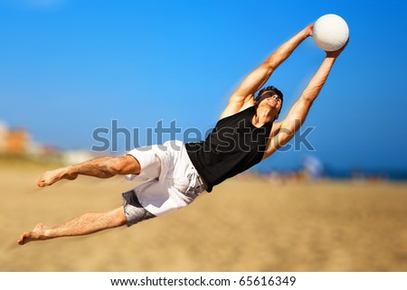 Young man playing soccer on beach. - stock photo