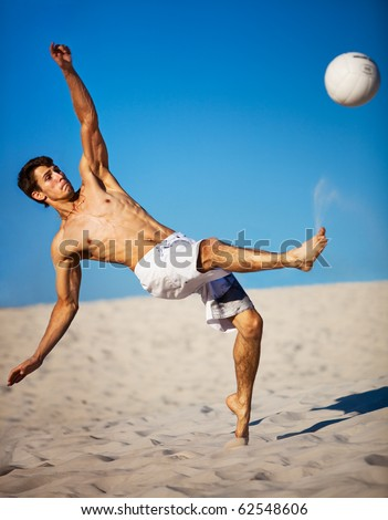 Young man playing soccer on beach. Focus on face.