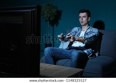 Young man playing video game at home in the evening