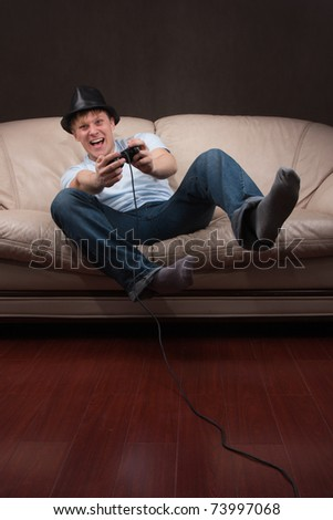 Young man playing video games on gray background