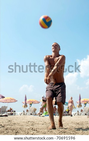young man playing volleyball on a beach.