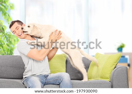 Young man playing with a puppy seated on couch at home