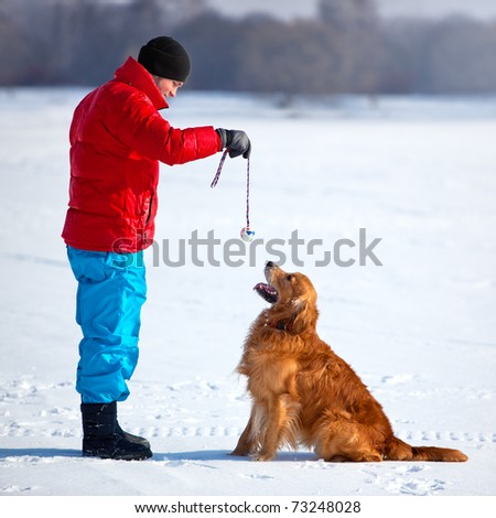 Young man playing with dog outdoors.