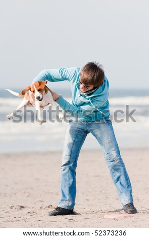 Young man playing with his beagle puppy