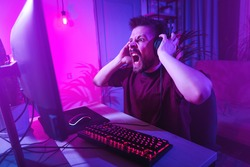 Young man plays computer games at home. The player is upset about the defeat. The streamer is angry during the broadcast. Neon studio setting. Guy surfing the Internet with headphones