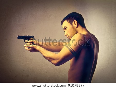 Young man pointing a gun - stock photo