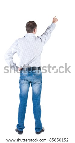 young man pointing at wall. rear view. Isolated over white .