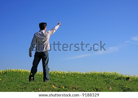 Young man pointing with his finger to the blue sky
