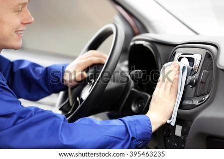 Young man polishing vehicle interior