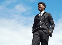 young man portrait blue sky suit and tie standing businessman leader low angle view