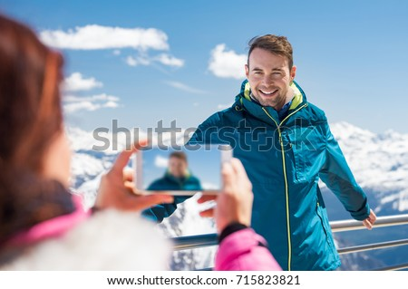 Young man posing for photo with mountains covered by snow. Young woman clicking boyfriend photo on snowy mountain in winter vacation. Smiling couple enjoying holiday during winter.