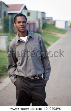Young man posing in the street of shack town.