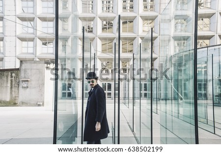 Young man posing with a trendy outfit against a urban background #638502199